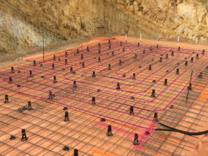 Hydronic infloor heating and cooling with geoexchange solution
